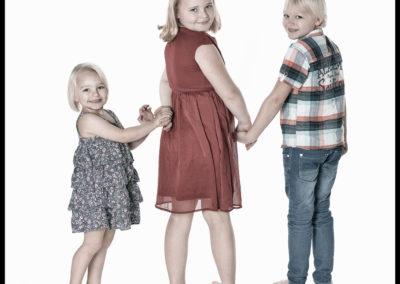 Børnefoto tre søskende holder i hånd og kigger bagud