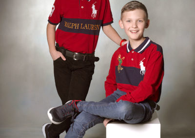 Børnefoto af to drenge den enes sider ned og mens den anden står op og holder ham på skulderen.
