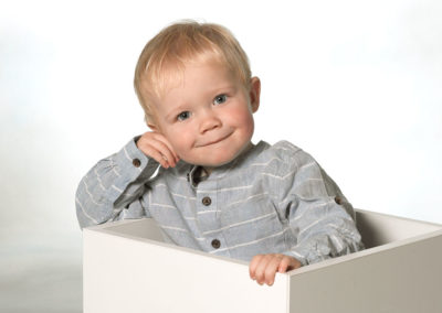 Børnefoto af dreng i kasse som læner sig på kanten