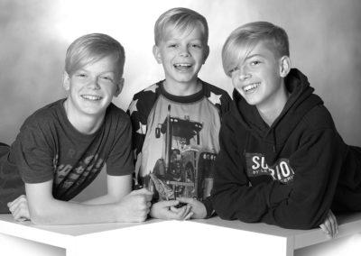 Børnefoto af 3 glade søskende i sorthvid