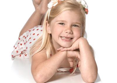 Børnefoto af storsmilende pige liggende på maven iført hvid kjole med røde prikker