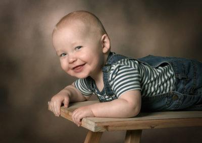Børnefoto smilende dreng liggende på bænk