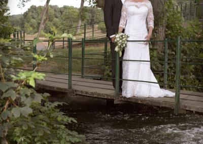 Bryllups foto med brudepar på bro gennem naturlige omgivelser.