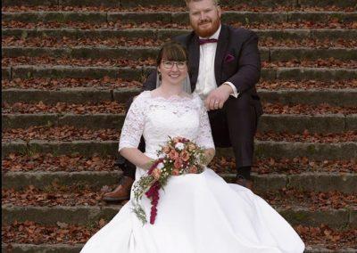 Bryllups foto brudepar på trappe med rød brune blade