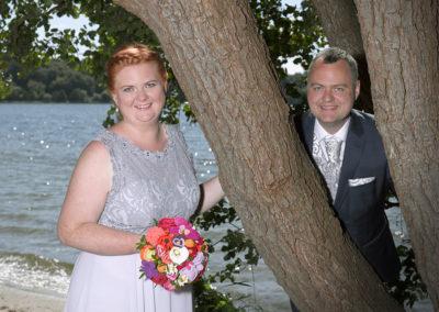 Bryllups foto af brudepar ved træ