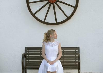 Konfirmationsbilleder med pige på en bænk