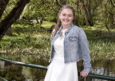 Konfirmationsbilleder af pige lænende op ad rækværket på en bro