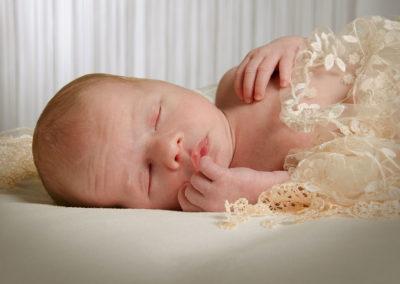 nyfødt foto baby sovende på ryggen med ansigtet frem